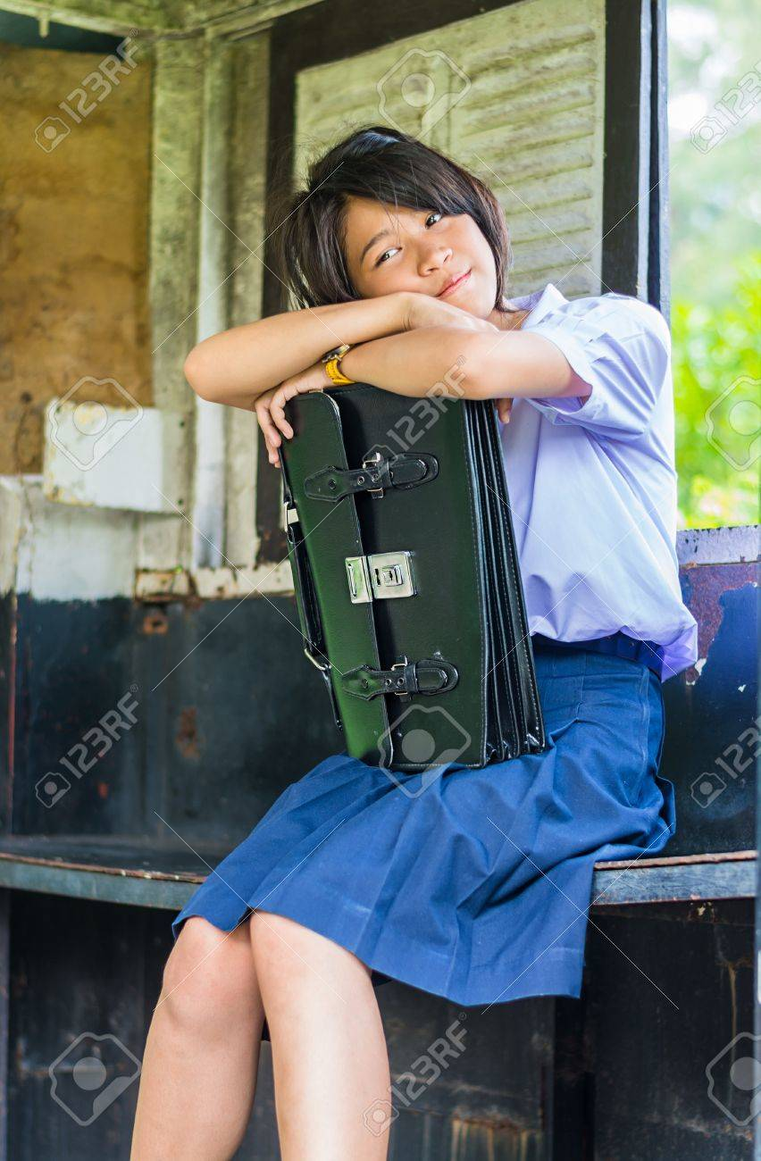 Cute Thai schoolgirl is daydreaming in an old bus stop  She is huging her school bag Stock Photo - 19225488