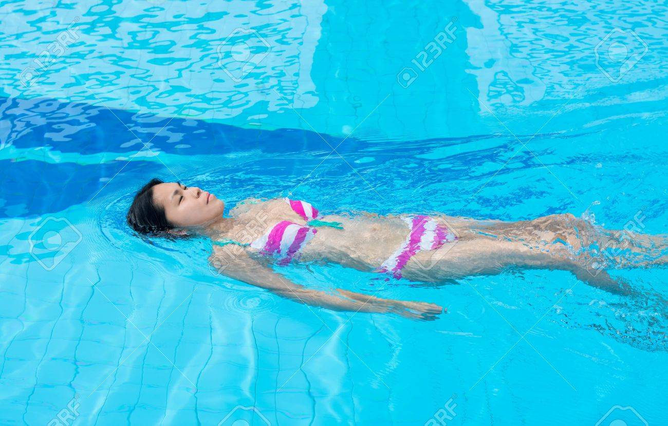 An Asian girl is swimming backstroke in the blue clean water of the swimming pool Stock Photo - 21492164