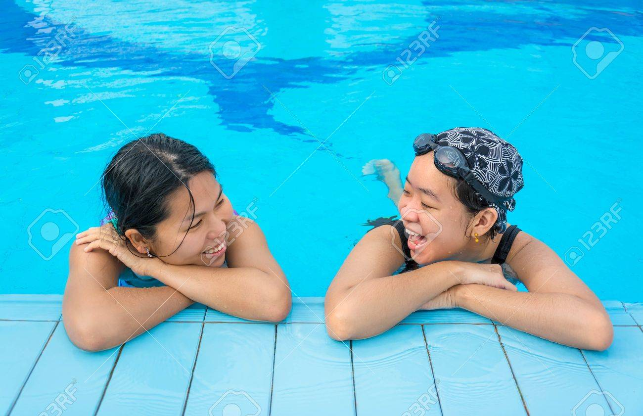 Two Asian girls are chatting in the swimming pool in holiday relaxation Stock Photo - 21964285