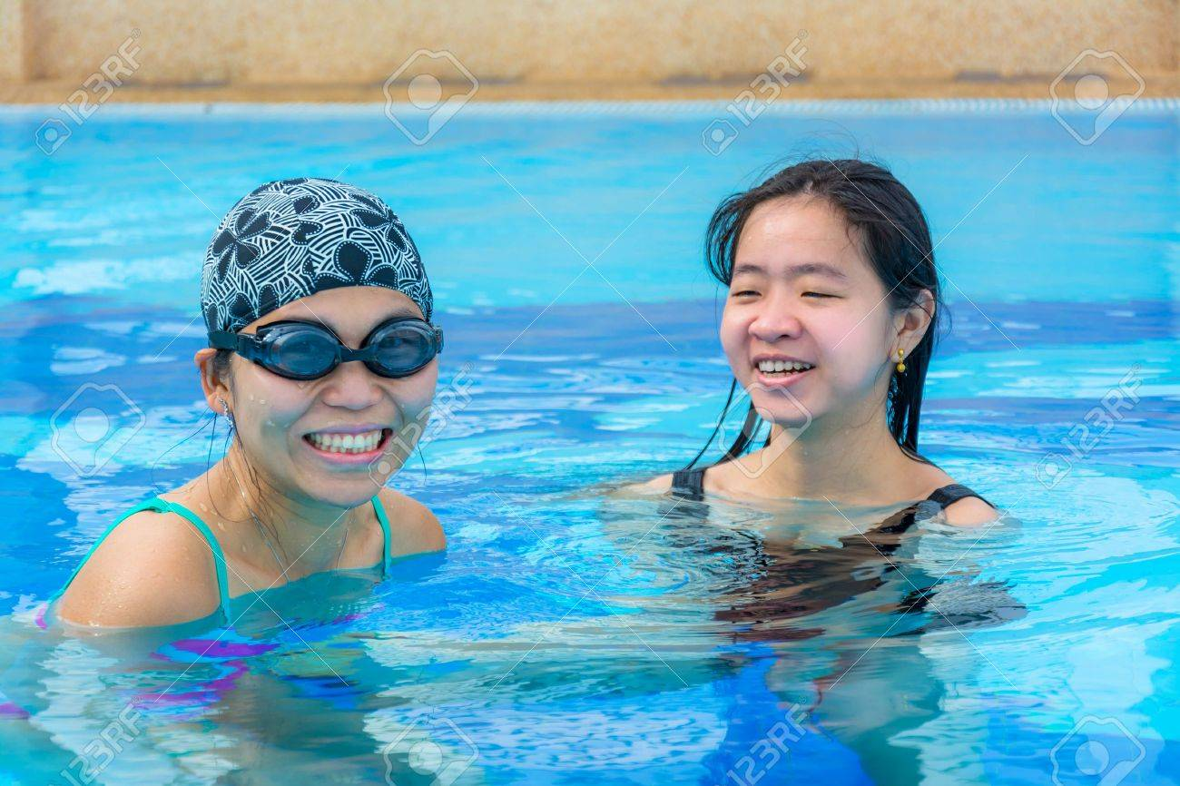 Two Asian girls are having fun floating in the swimming pool in holiday relaxation Stock Photo - 21845682