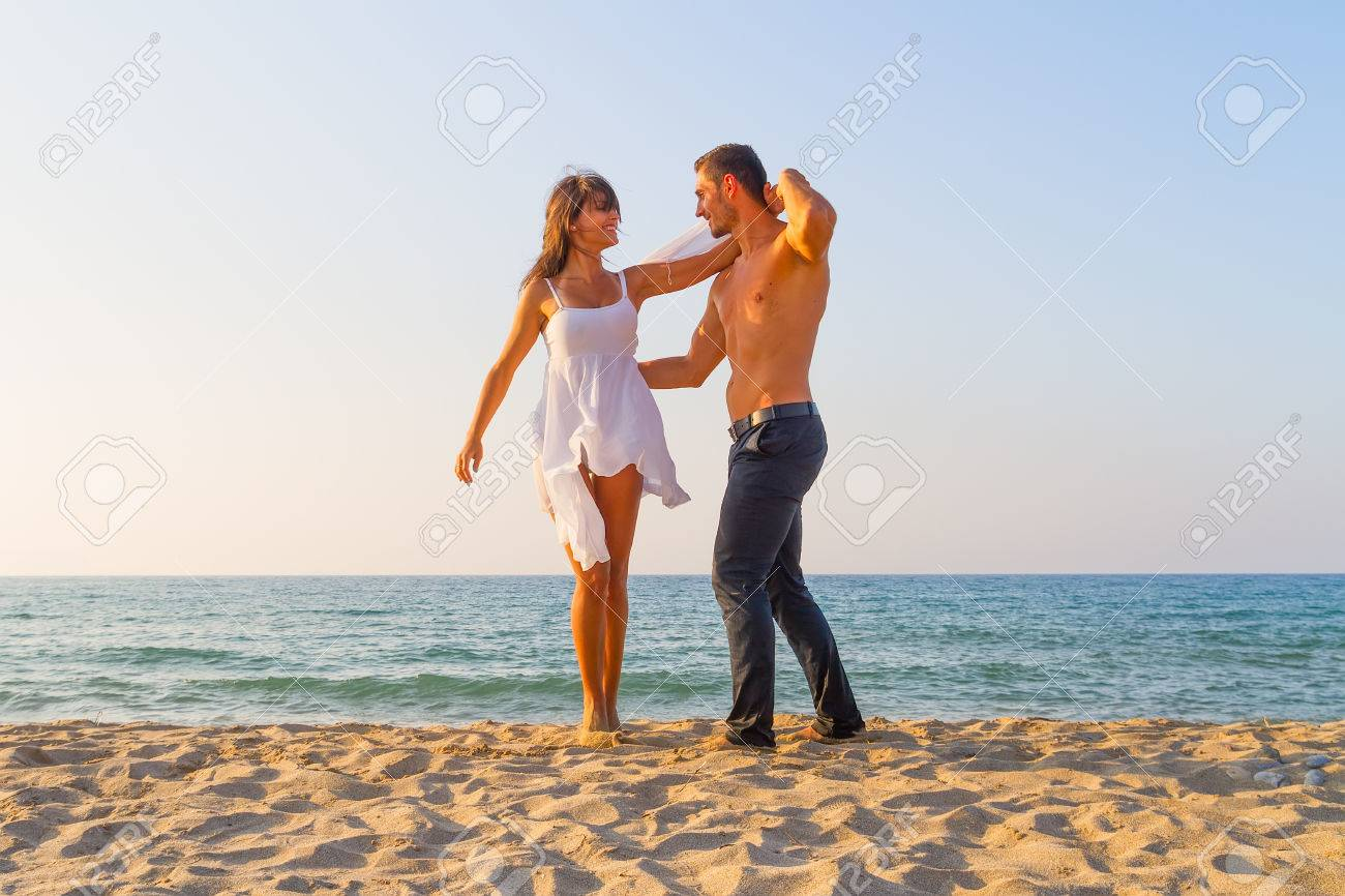 Young couple play on beach