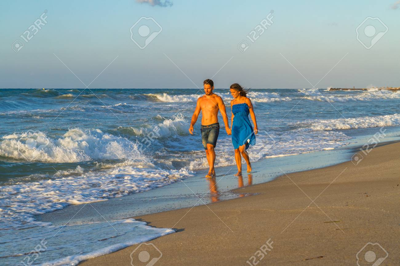 Happy young couple in jean shorts, a blue dress, walking along a wet sandy