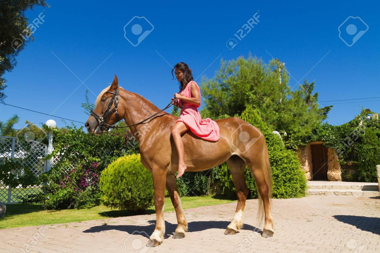schöne junge barfuß moderne brünette amazon mit roten kleid, auf einem  schlanken braun blond reinrassige pferd ohne sattel.