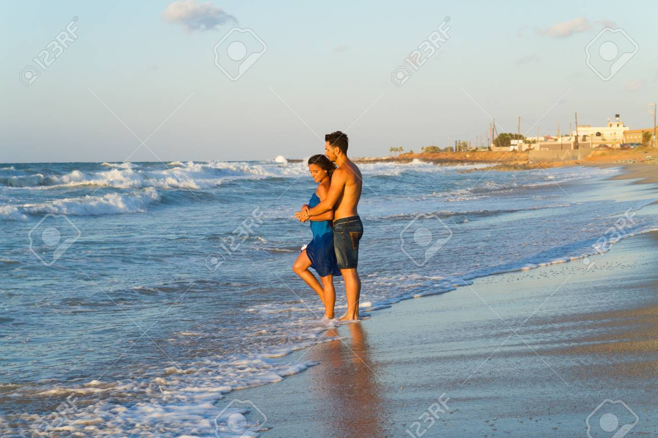 Happy young couple in jean shorts and a blue dress, having fun walking  along a