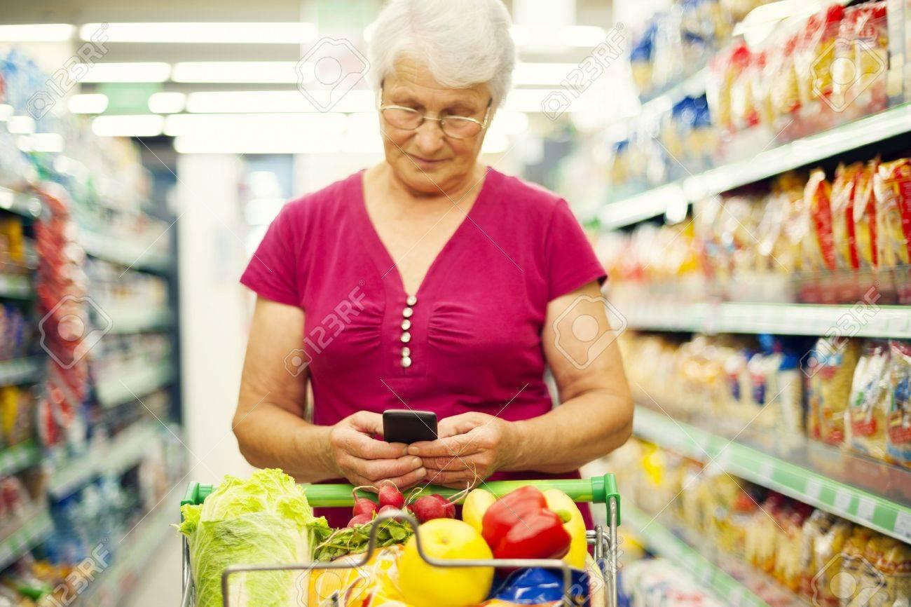 Senior woman texting on mobile phone at supermarket Stock Photo - 18184380