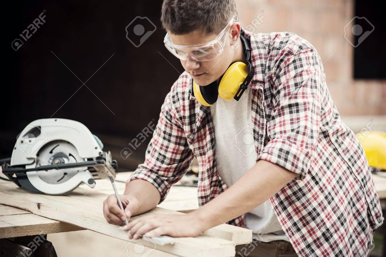Carpenter measuring a wooden plank Stock Photo - 18184889