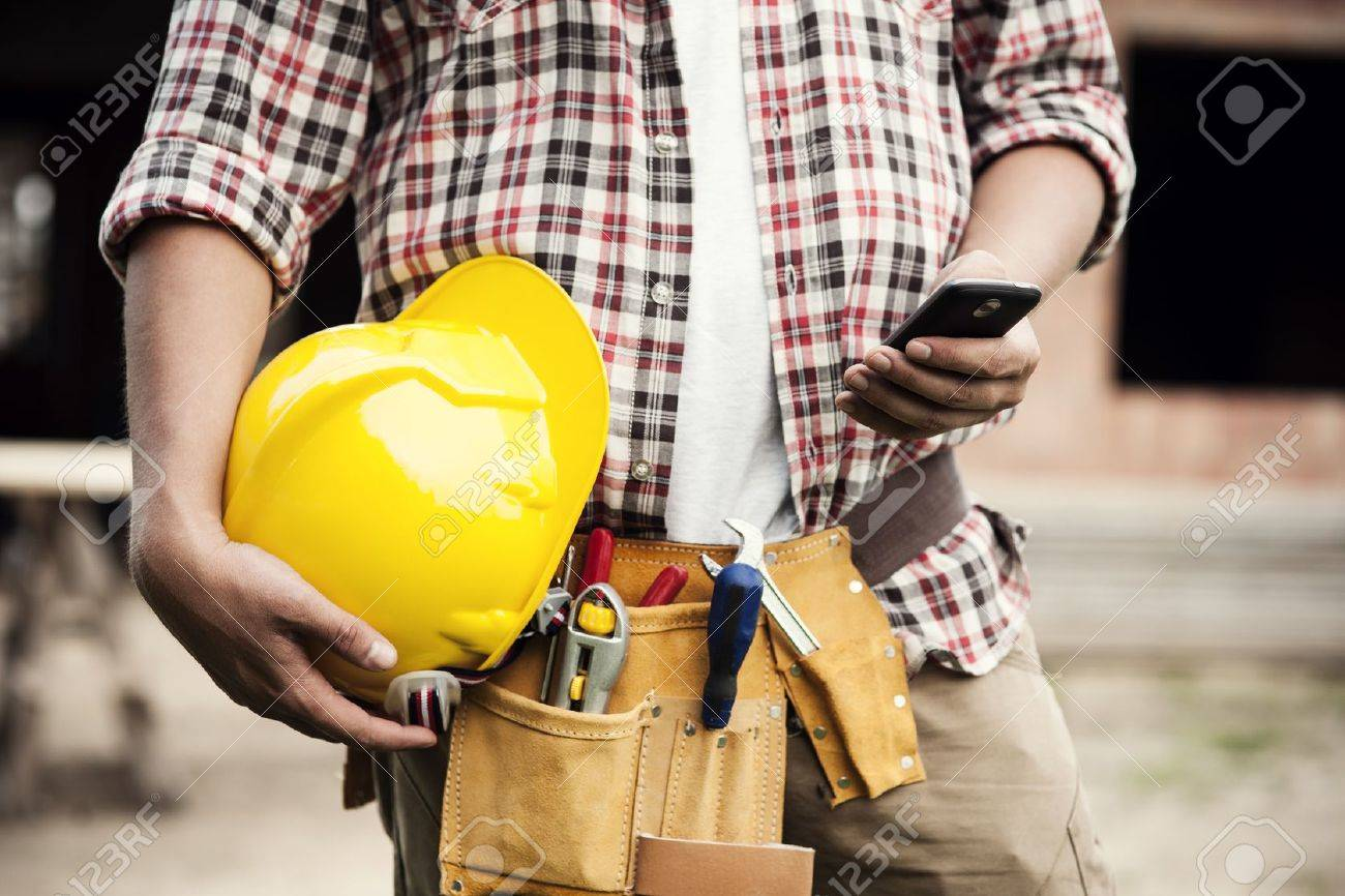 Close-up of construction worker texting on mobile phone Stock Photo - 18184878
