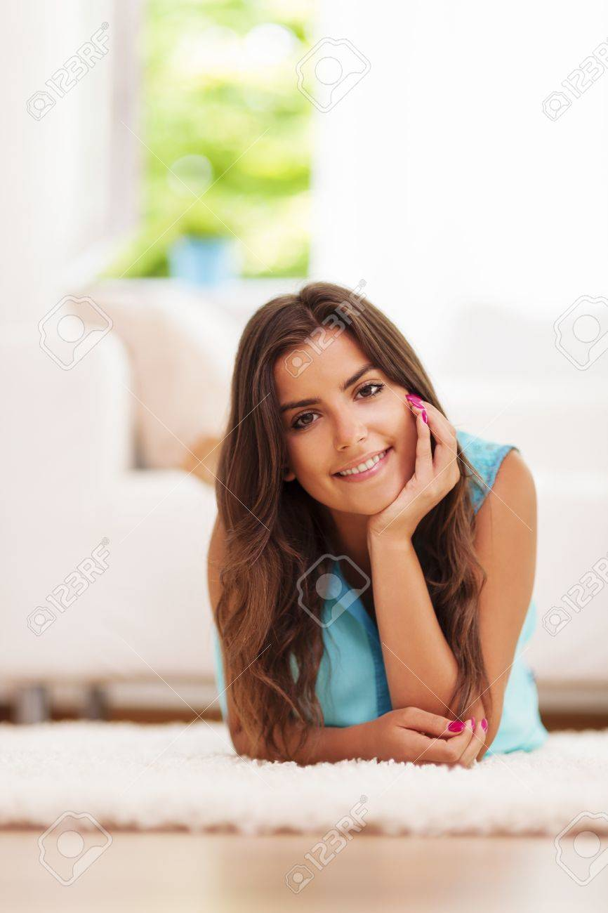 Charming young lady lying down on the carpet and resting Stock Photo - 21025473
