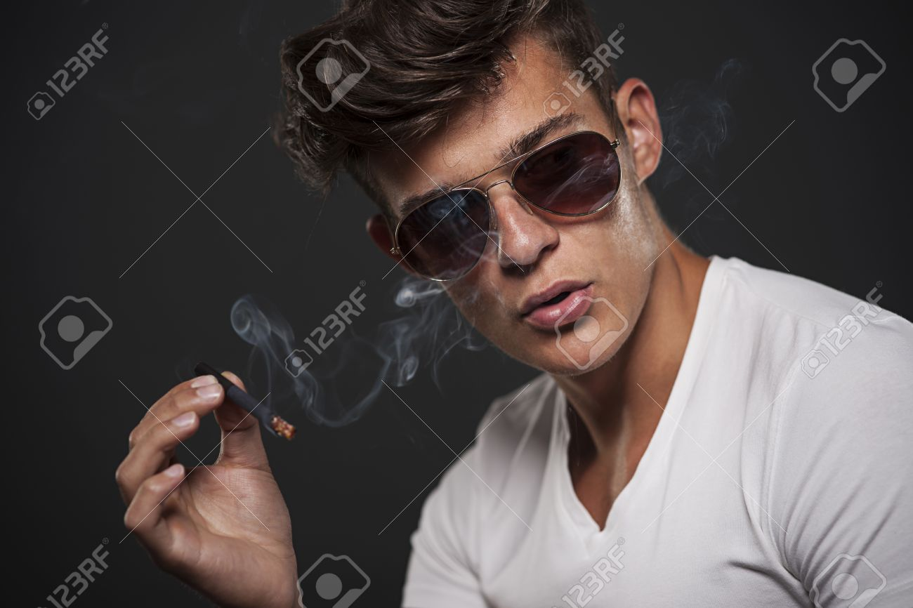 Handsome young man smoking cigarette Stock Photo - 22225237