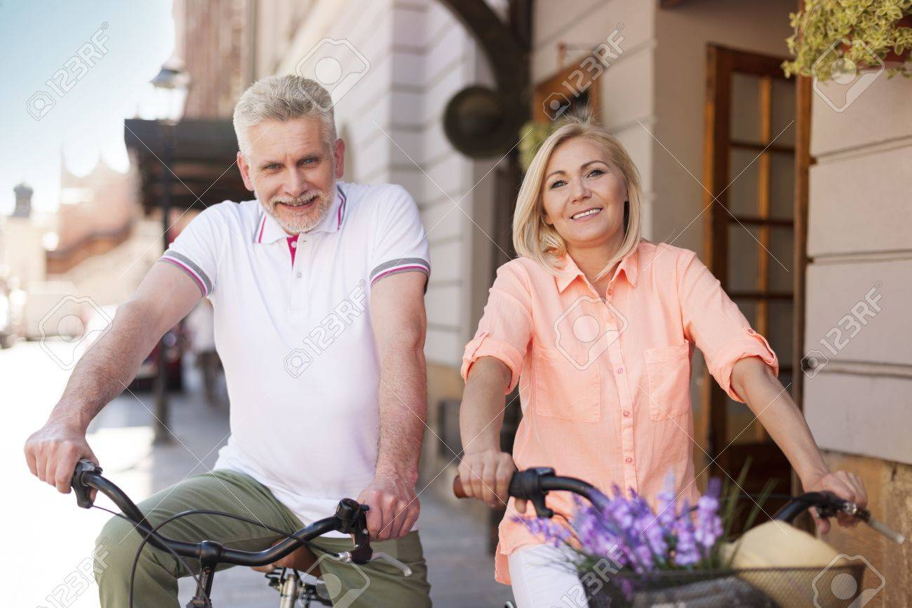mature couple riding on bike in city stock photo, picture and