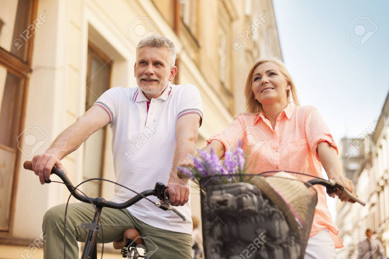 active mature couple riding on the bike in city stock photo, picture