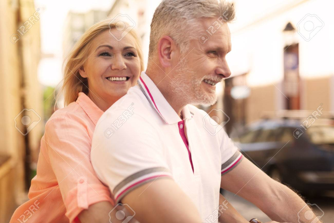 close up of loving mature couple riding on bike stock photo, picture