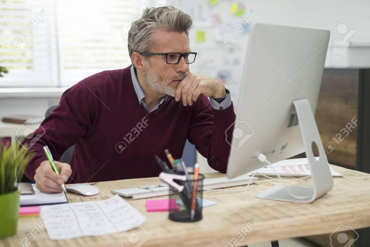 Pensive man working hard on computer Stock Photo - 49257849