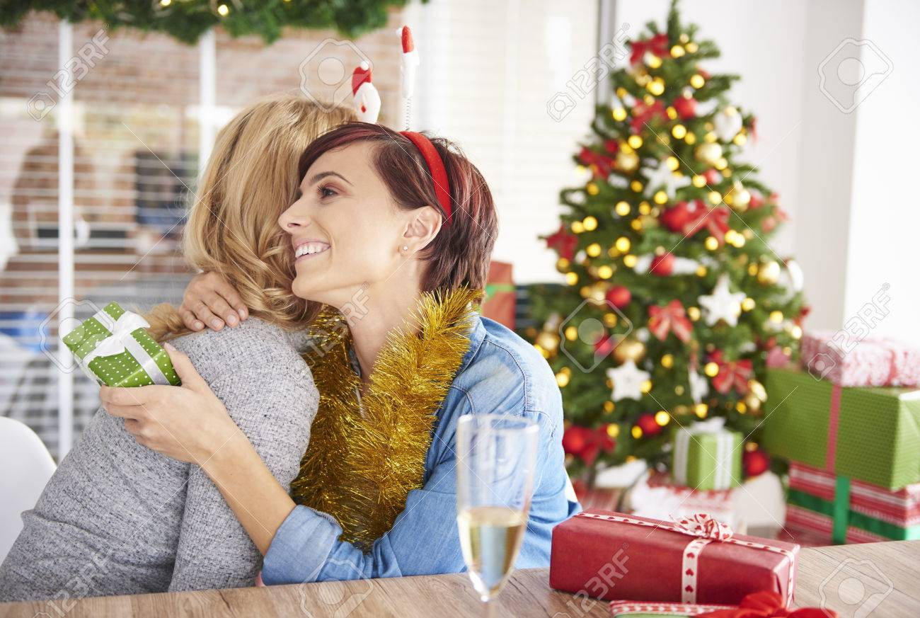 exchanging christmas gifts by two young women stock photo 65197688