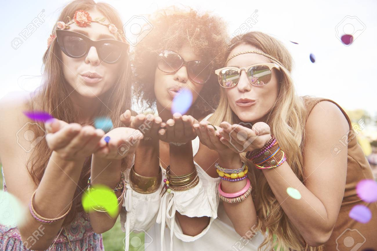 Girls blowing some confetti pieces Stock Photo - 66133853