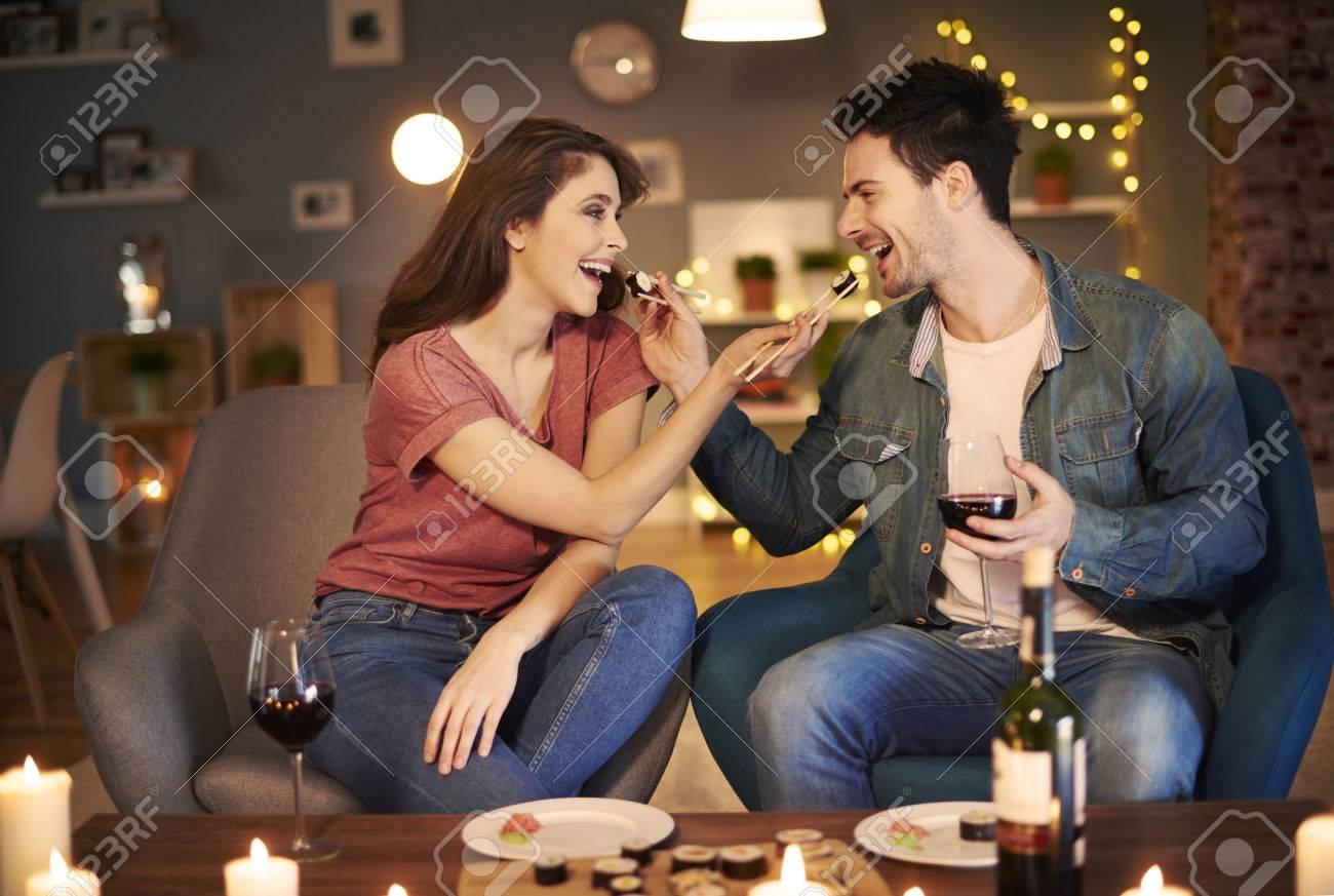 Couple feeding each other over dinner - 73083638