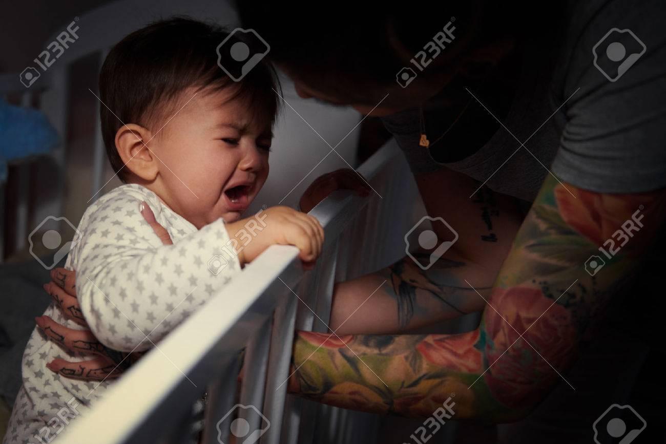 Mummy lulling baby to sleep - 75236249