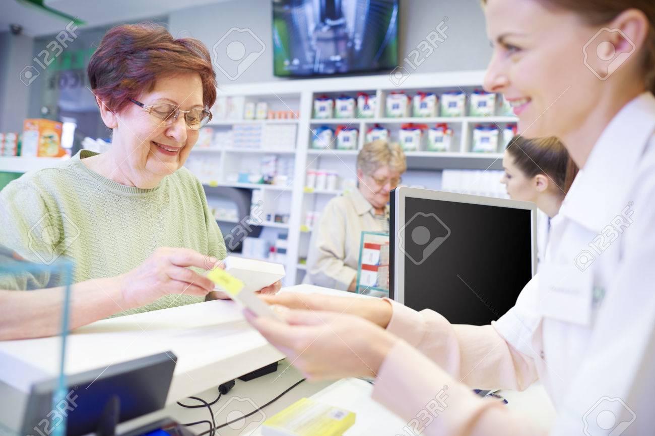 Young pharmacist explaining dose to female senior - 75945170