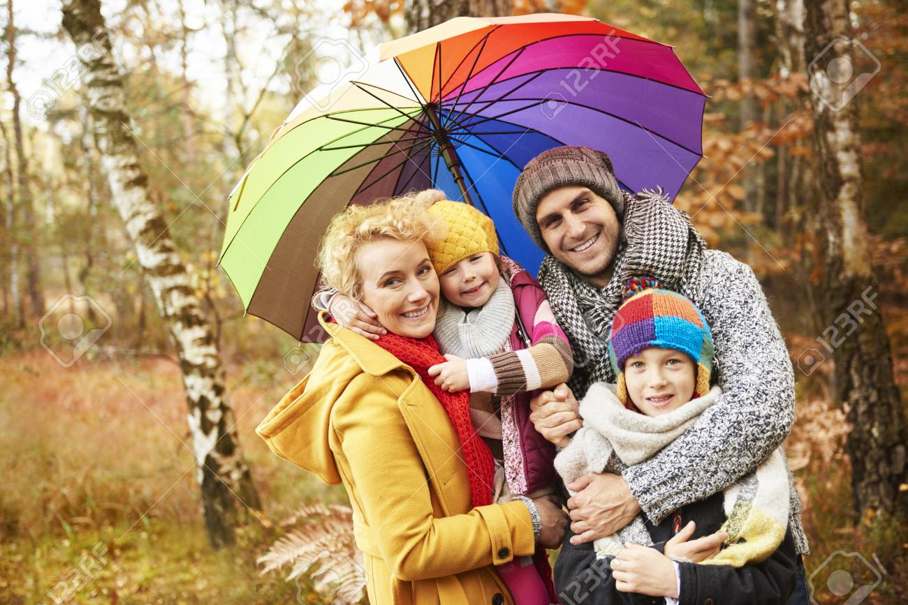 Family looking for shelter with umbrella - 82526428