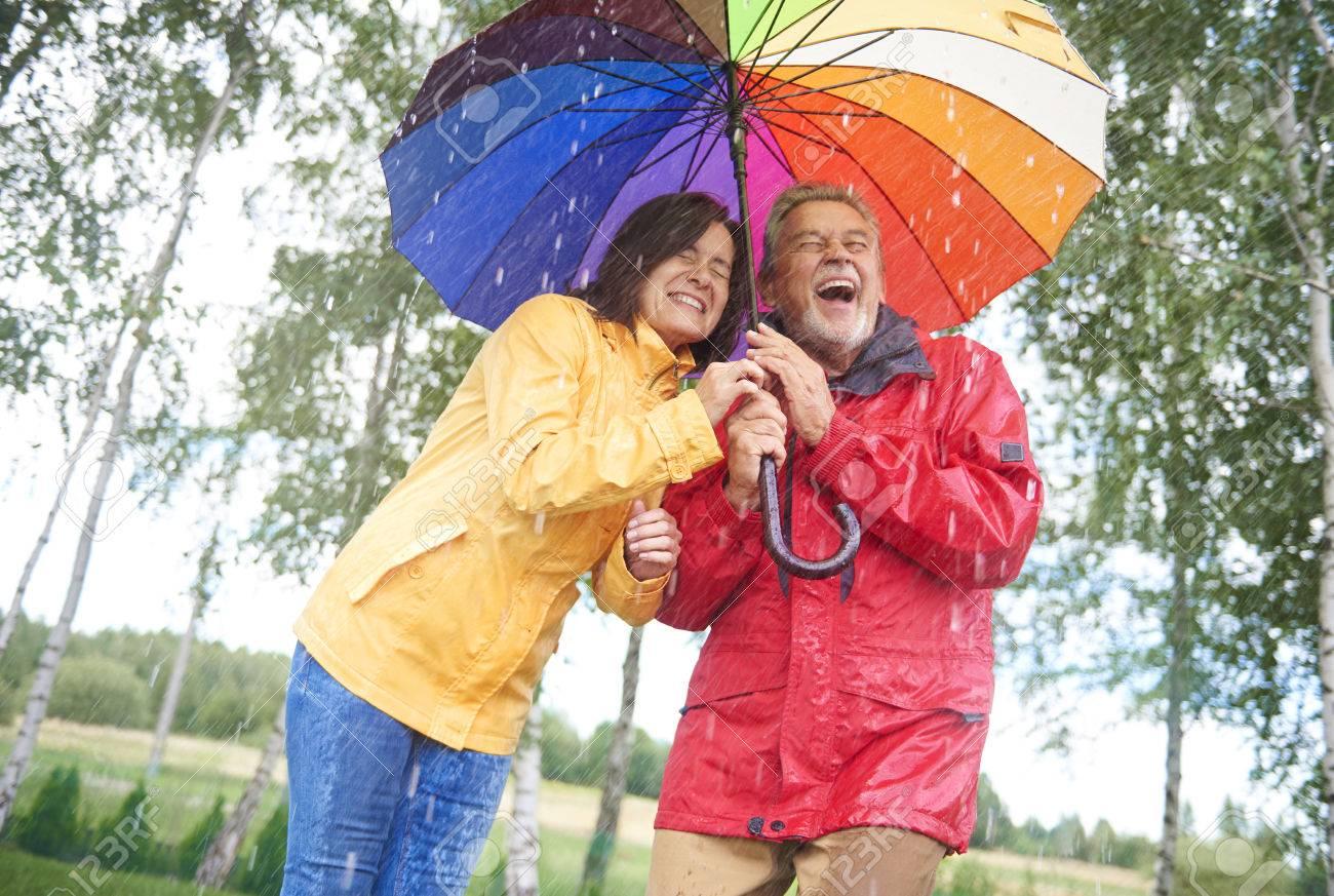 Wet couple hiding under colorful umbrella - 84171321