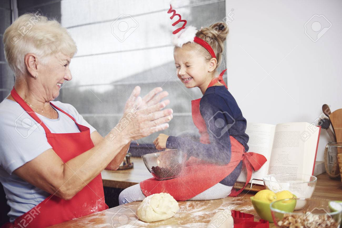 Grandmother and granddaughter enjoying in kitchen - 84317541