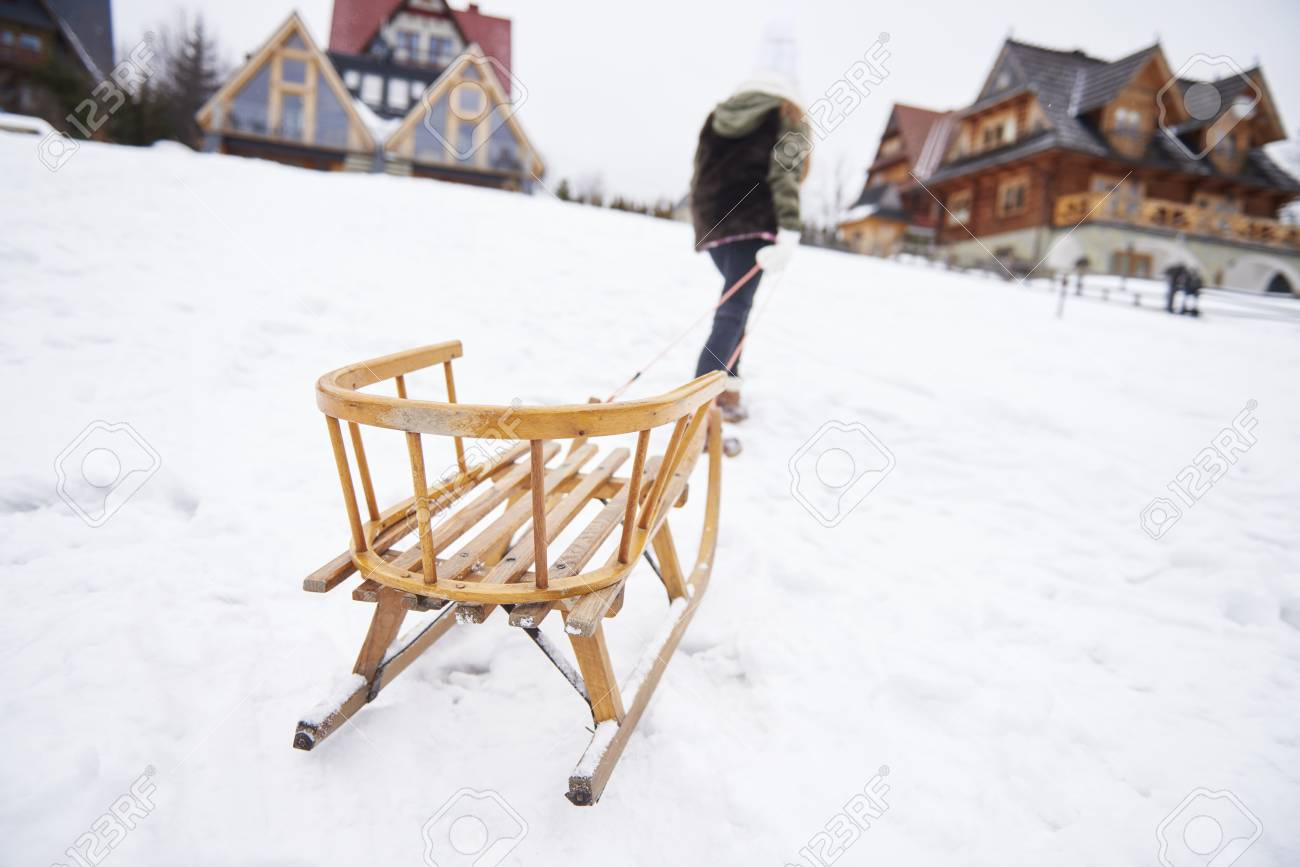 man pulling sleigh up the hill stock photo picture and royalty free