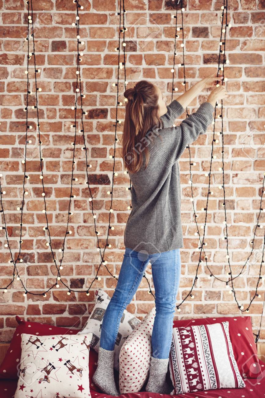 What Can I Use To Attach Christmas Lights To Brick woman standing on bed and hanging christmas lights
