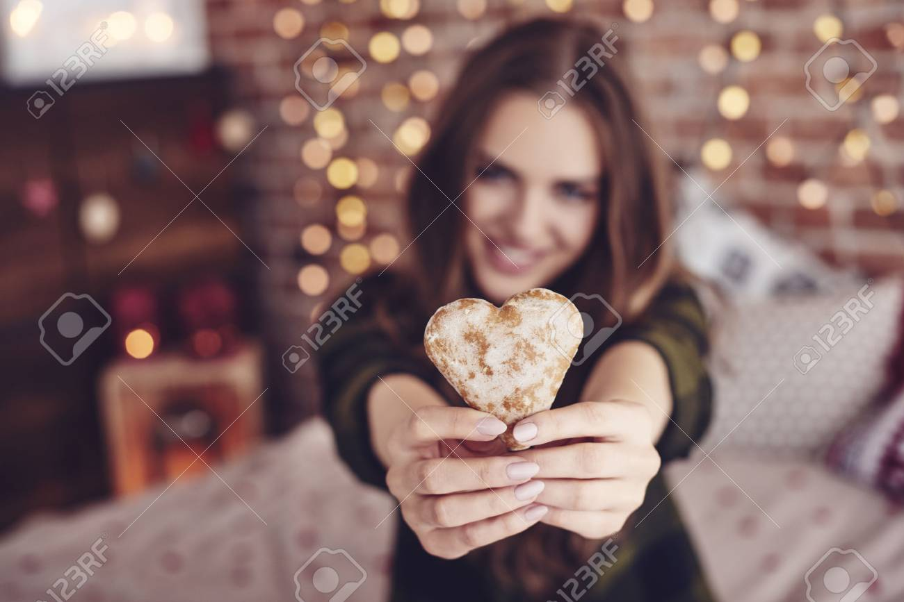Heart-shaped cookie in human hand - 87481386