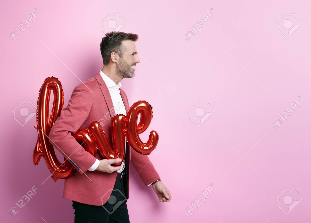 Cheerful man helping to preparing decorations for valentine's party - 89280198