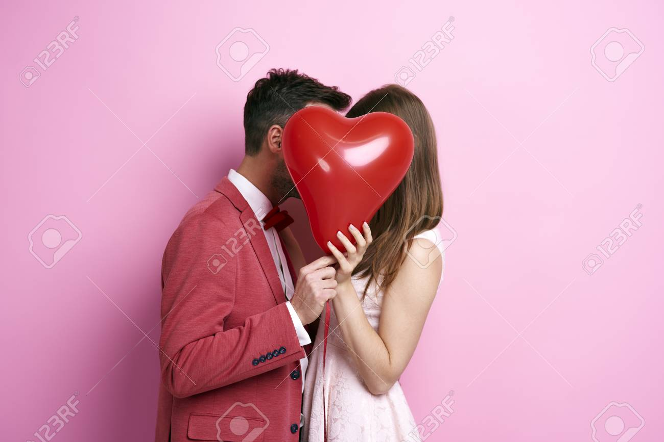 Affectionate couple covering face with balloon and kissing - 89327683