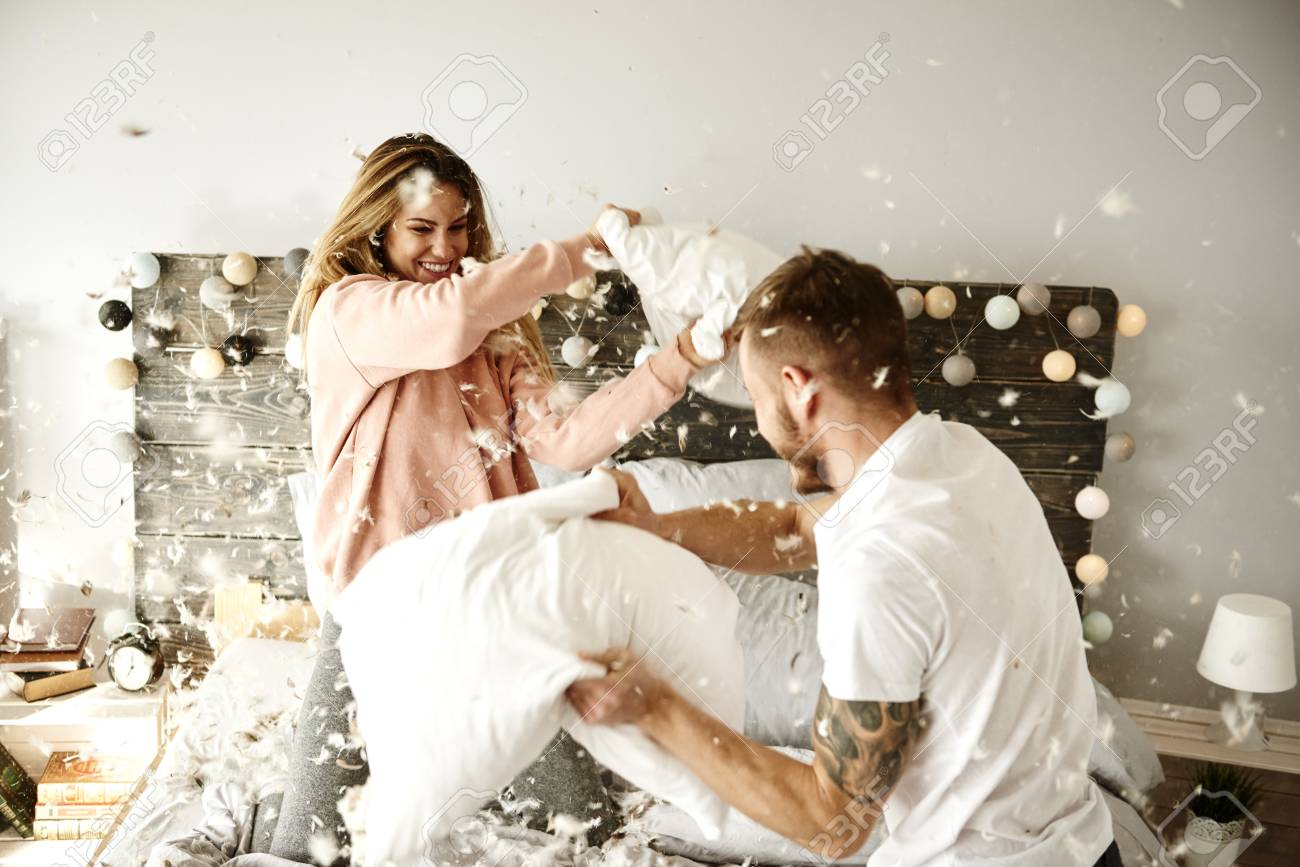 Couple having a fun while pillow fight - 93198841