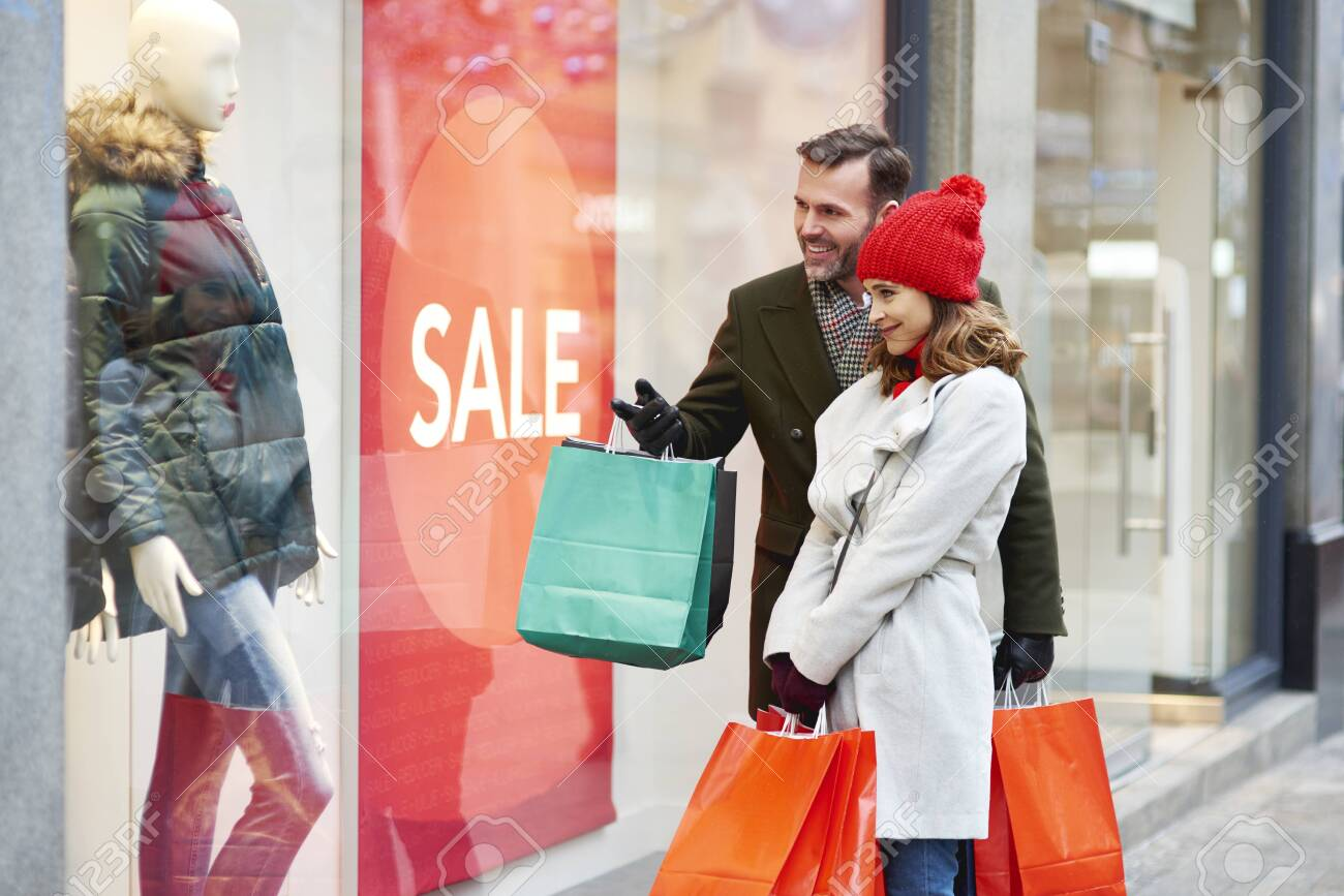 Happy couple looking at big shop display - 133550248