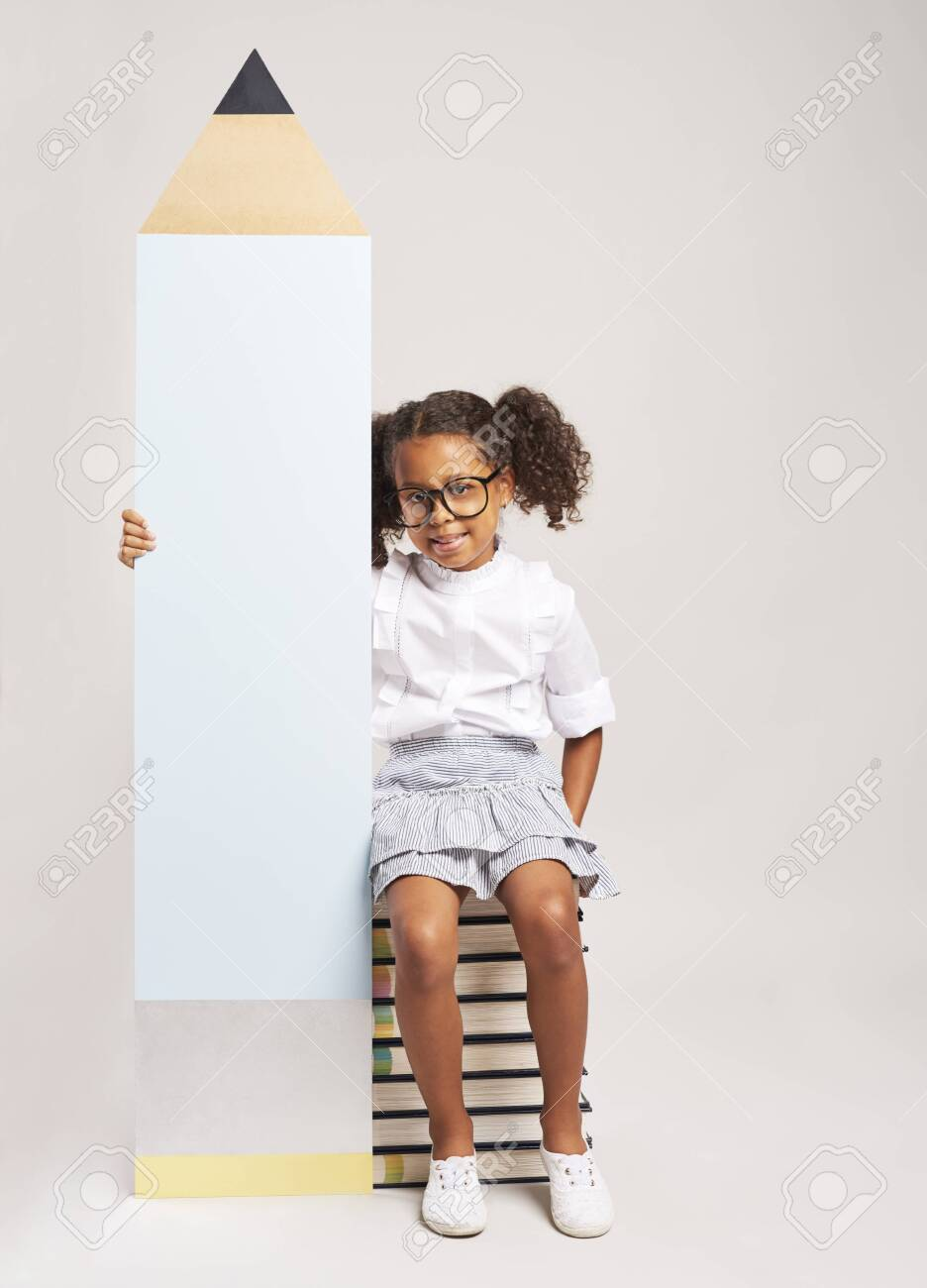 African girl sitting on books and holding big pencil - 137354186
