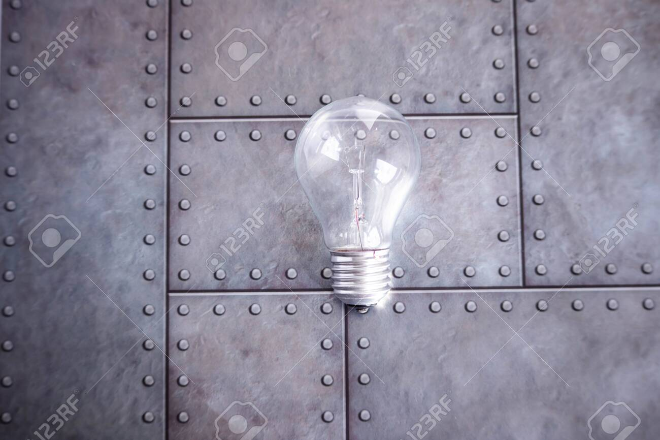An electric glass bulb lies on a gray iron background. Free space for text. - 154323548