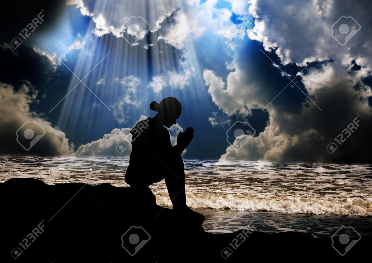 Silhouette of young girl praying peacefully Stock Photo - 31639657
