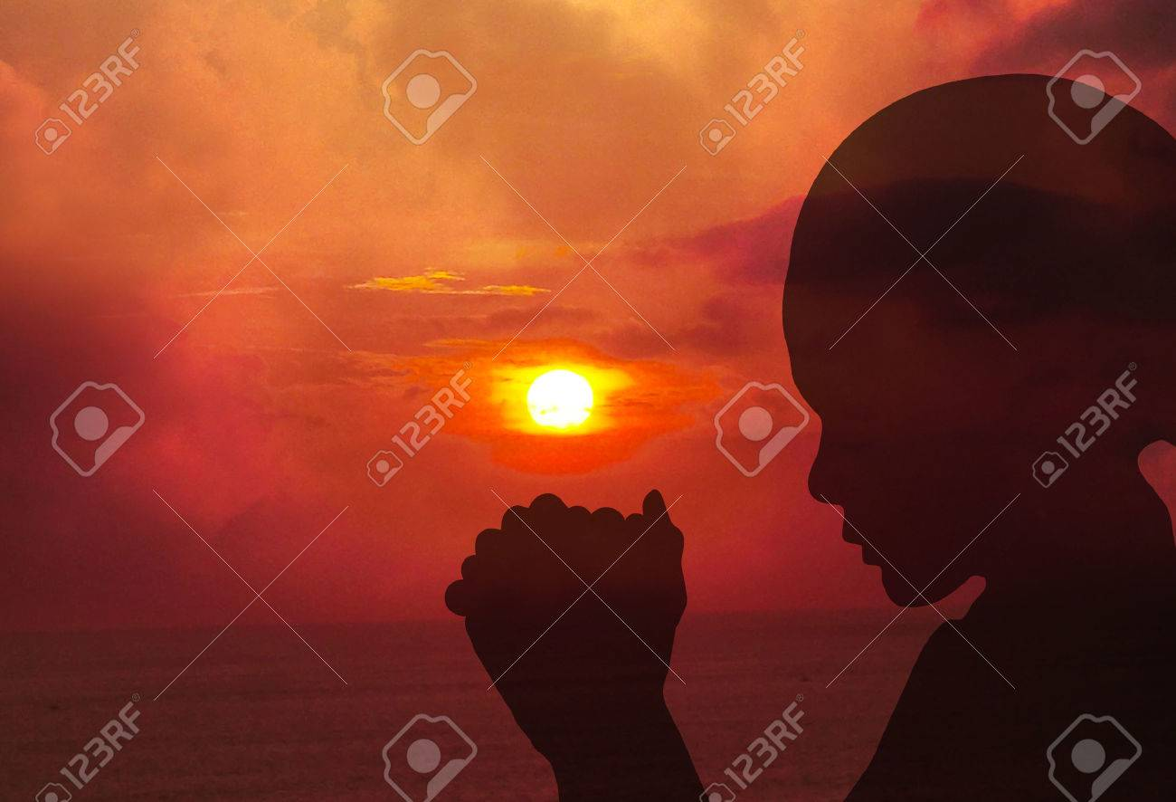 Silhouettes of a women praying at sunset Stock Photo - 42525897