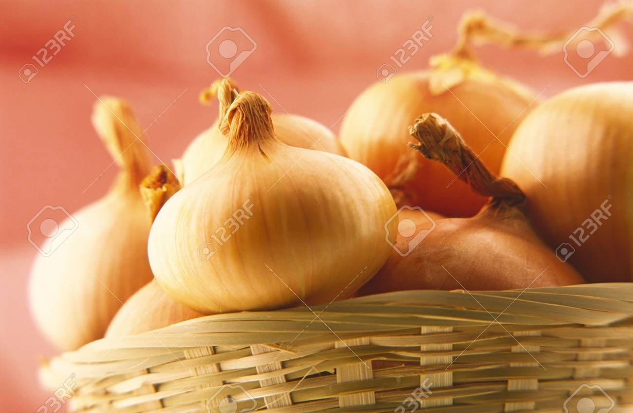 basket of onions on  red background Stock Photo - 828089