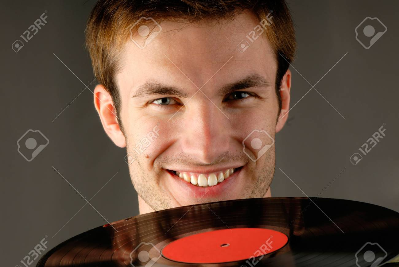 guy holds in hands vinyl record on  gray background Stock Photo - 2025575