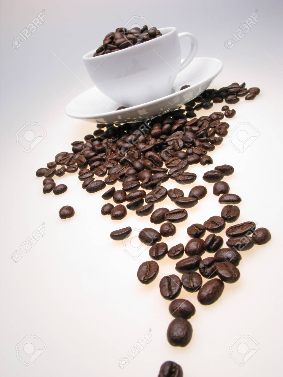 white color  cup and  plate filled with grains of coffee on  white background Stock Photo - 2273499