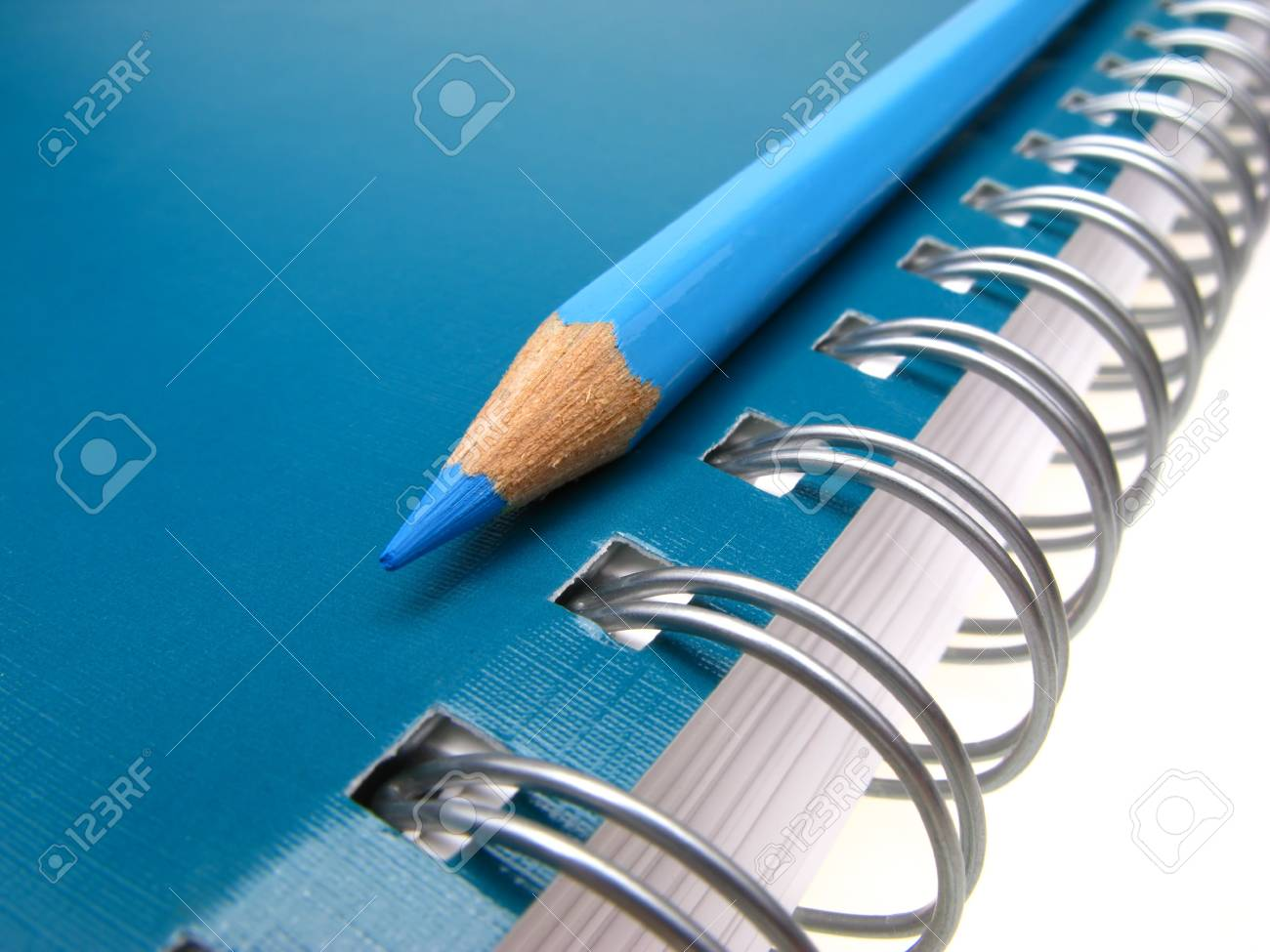 blue pencil and spiral of  notebook on  light background,  close up Stock Photo - 2338717