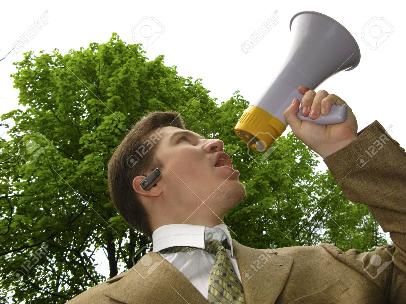 young businessman shouts in megaphone on  background of  green tree Stock Photo - 3020848