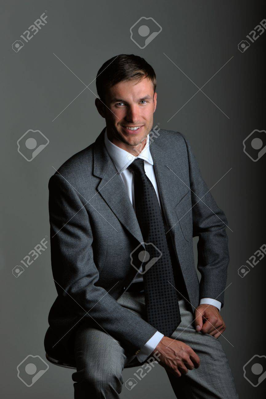 portrait young serious businessman, looks in chamber, on gray background Stock Photo - 5690461