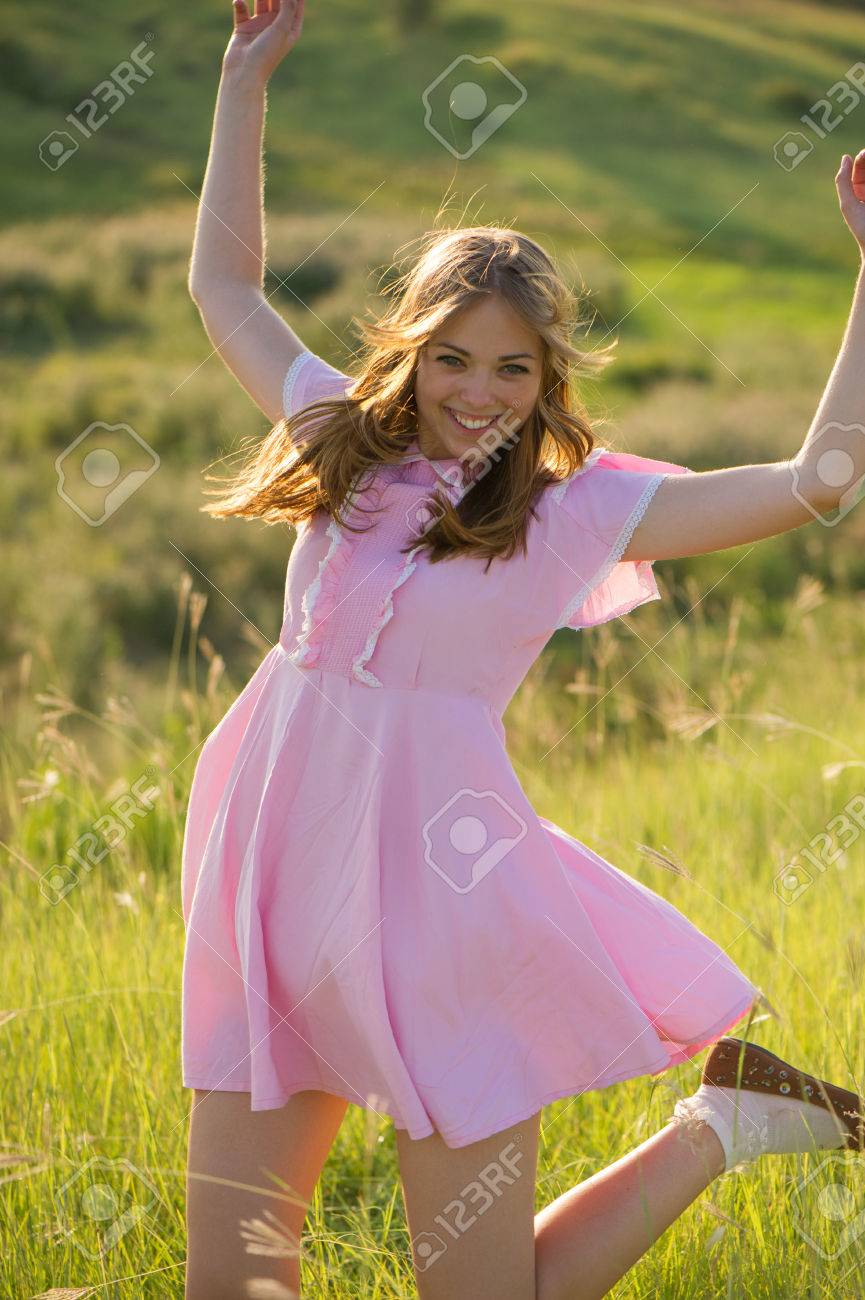 Beautiful Girl In A Pink Dress With Her Hair Dancing In Nature