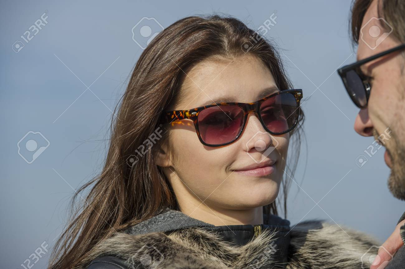 08efe5491d1b pretty girl in sunglasses smiles at the guy. A girl with her hair loose  flirts