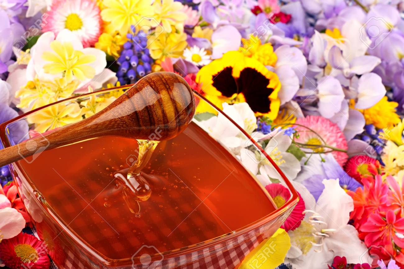 Glass pot with honey with many flowers Stock Photo - 10061376