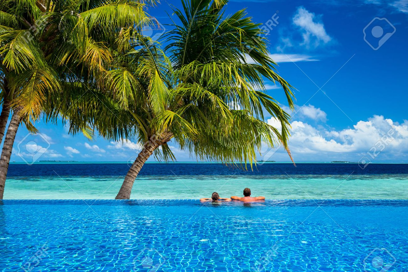 young couple relaxing in infinity pool under coco palms in front of tropical landscape - 42736512