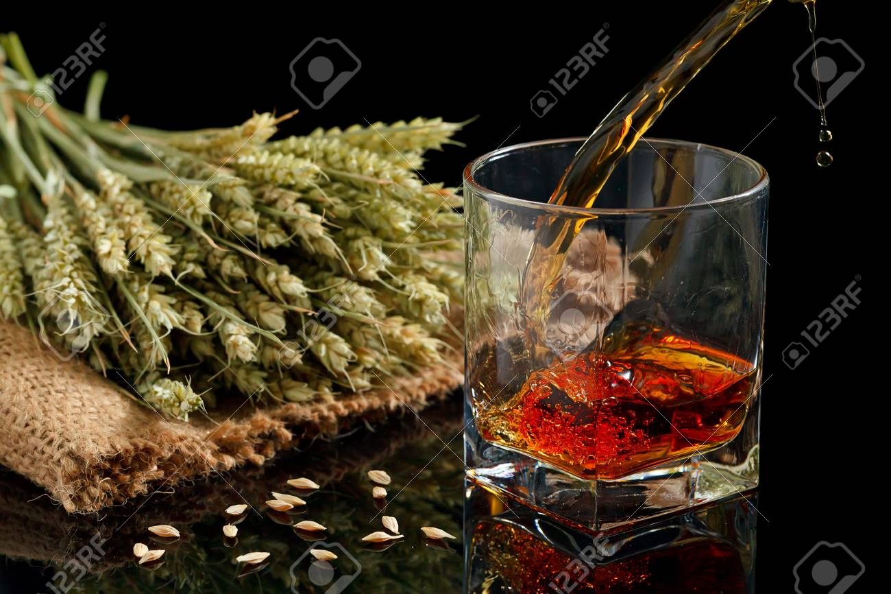 Pouring whiskey into glass, on black background Stock Photo - 20867592