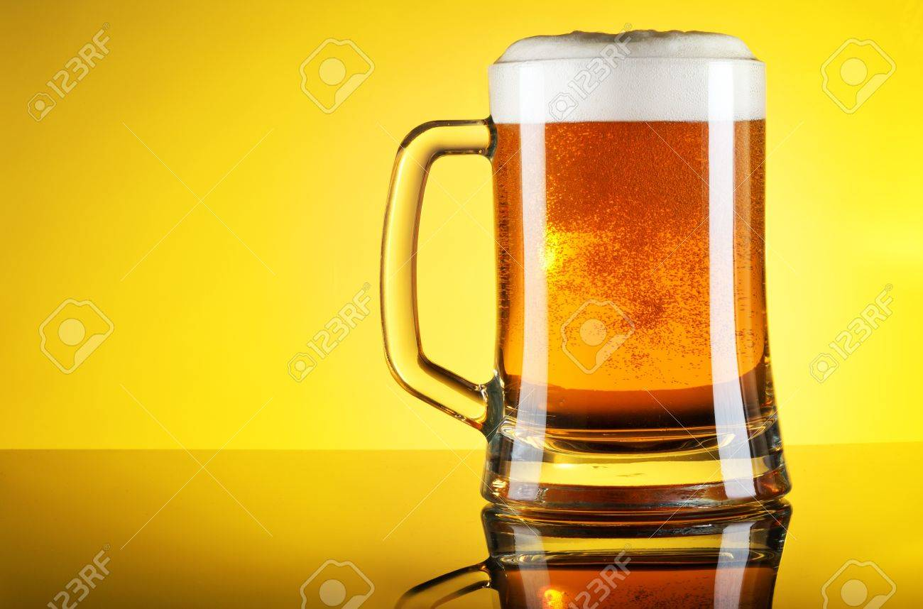 Glass of beer close-up with froth over yellow background Stock Photo - 20871697