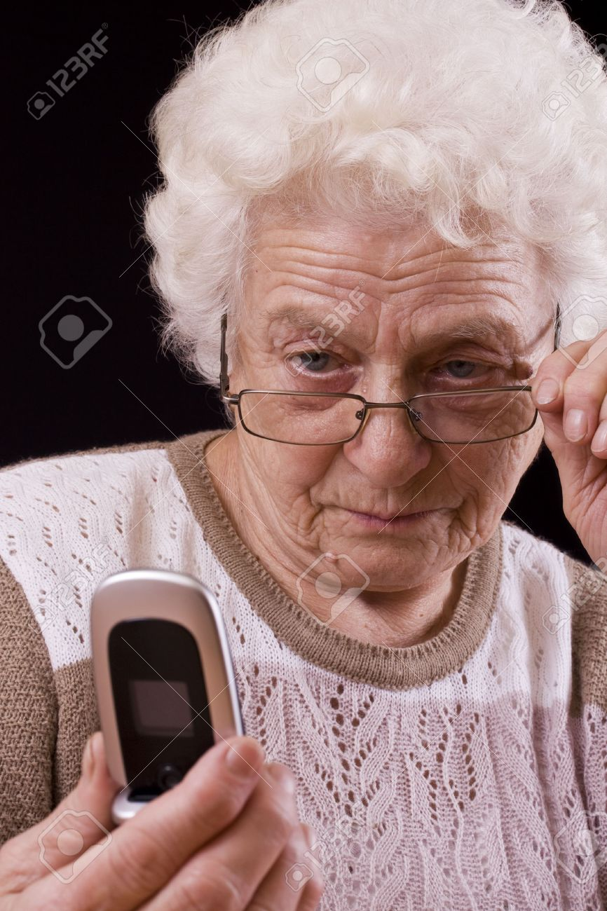 Old woman and the mobile phone isolated in black background Stock Photo - 7172368