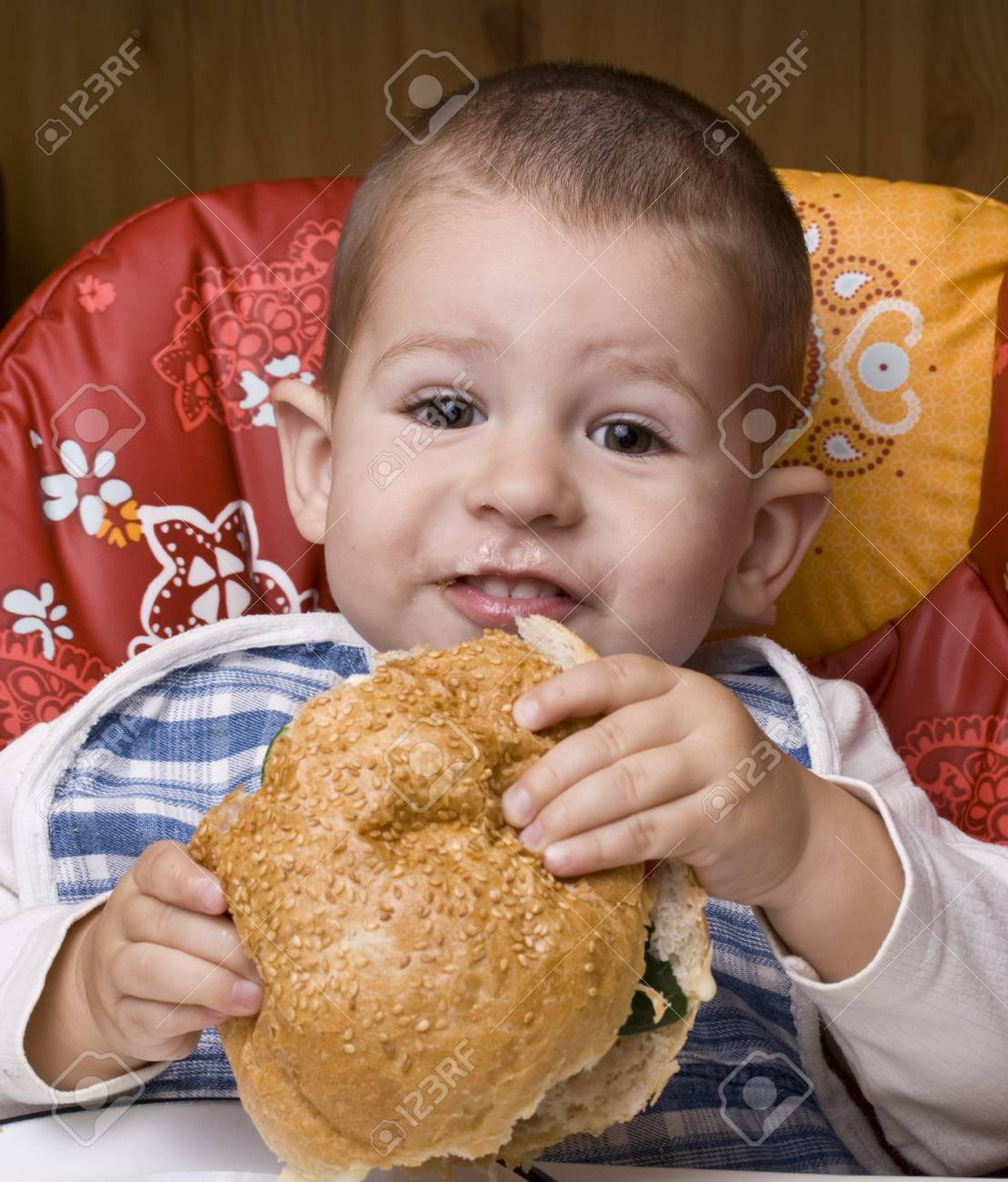 The little happy boy eating a tasty hamburger Stock Photo - 8306621